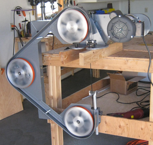 Frictionless Tension and Tracking assembly on this three-wheeled portable band saw